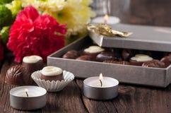 Bonbons au chocolat, bougies et fleurs Photo stock