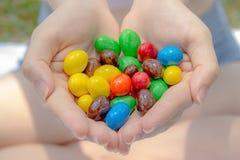 Bonbons au chocolat colorés en main de jolies femmes ou fille Image libre de droits