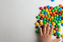Bonbons au chocolat colorés sur le fond blanc avec la main d'enfant images stock