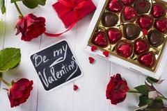 Bonbons au chocolat délicieux dans le boîte-cadeau sur le fond en bois blanc Image libre de droits