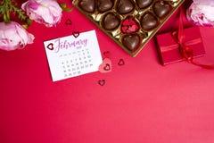 Bonbons au chocolat délicieux dans le boîte-cadeau sur le fond rouge Photos libres de droits