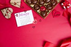 Bonbons au chocolat délicieux dans le boîte-cadeau sur le fond rouge Photographie stock