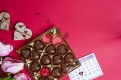 Bonbons au chocolat délicieux dans le boîte-cadeau sur le fond rouge Images stock