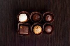 Bonbons au chocolat délicieux sur le fond en bois Image libre de droits