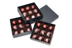 Bonbons au chocolat dans les giftboxes d'isolement sur le fond blanc Confiserie assortie de chocolats dans leurs boîte-cadeau Ens Photographie stock libre de droits