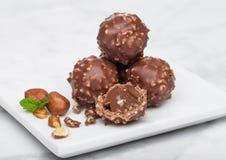 Bonbons au chocolat de luxe avec les morceaux de noisettes et la feuille en bon état sur le conseil de marbre photo libre de droits