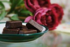 Bonbons au chocolat en gros plan sur un fond des fleurs images stock
