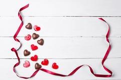Bonbons au chocolat et lucettes rouges avec le ruban rouge de satin Photographie stock libre de droits