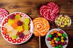 Bonbons au chocolat, lucettes et bonbons colorés à gelée sur la table en bois images stock