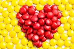 Bonbons au chocolat rouges à lait de forme de coeur avec le backg jaune de sucreries Photos stock