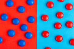 Bonbons au chocolat rouges et bleus vitrés sur le backgro coloré lumineux images stock