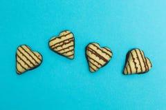 Bonbons au chocolat sous forme de coeur d'isolement sur le fond bleu photographie stock
