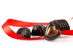 Bonbons au chocolat sous forme de coeur et ruban rouge sur un fond blanc Photos stock