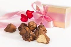 Bonbons au chocolat sur un fond des deux coeurs rouges troubles et d'un g Image libre de droits