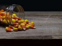 Bonbons au maïs se renversant hors d'un pot en verre sur une table en bois photo stock