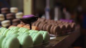 Bonbons colorés appétissants à macaron à la fenêtre de confiserie, dessert délicieux clips vidéos