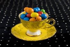 Bonbons colorés dans la tasse de thé de cru Photo stock