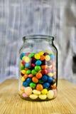 Bonbons colorés dans le pot Photo stock
