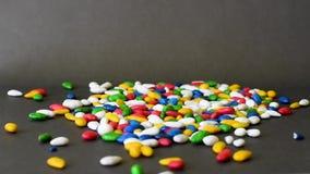 Bonbons colorés sur un fond noir de table banque de vidéos