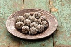 Bonbons crus faits maison à vegan dans des copeaux de noix de coco dans le plat en céramique o images libres de droits