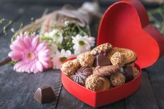 Bonbons délicieux en boîte rouge et fleurs Image libre de droits