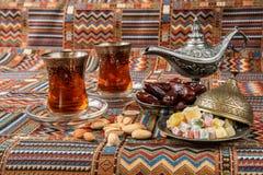 Bonbons, dates et thé sur un tapis Images stock