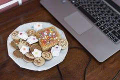 Bonbons et biscuits avec les visages gais, derrière un ordinateur portable sur une table d'acajou Photos libres de droits
