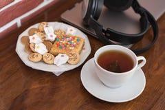 Bonbons et biscuits avec les visages gais, une tasse de thé parfumé derrière un ordinateur portable et écouteurs sans fil sur une Photos stock