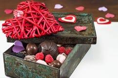 Bonbons et coeur décoratif de jour du ` s de Valentine dans une vieille boîte Plan rapproché, foyer sélectif Images stock