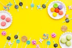 Bonbons für Parteihintergrund Macarons und Lutscher auf gelber Draufsicht kopieren Raum Stockfotografie