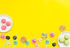 Bonbons für Parteihintergrund Macarons und Lutscher auf gelber Draufsicht kopieren Raum Stockbilder
