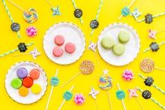Bonbons für Parteihintergrund Macarons und Lutscher auf gelber Draufsicht kopieren Raum Lizenzfreie Stockfotos