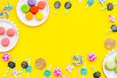 Bonbons für Parteihintergrund Macarons und Lutscher auf gelber Draufsicht kopieren Raum Stockfoto