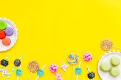 Bonbons für Parteihintergrund Macarons und Lutscher auf gelber Draufsicht kopieren Raum Lizenzfreie Stockfotografie