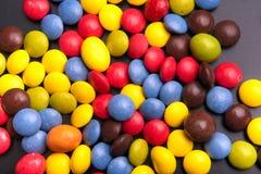 Bonbons faits au hasard colorés à chocolat d'isolement sur le gris Photos libres de droits