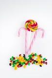 Bonbons - lucette colorée et rose avec le bâton blanc de rayures sur un fond blanc Photographie stock libre de droits