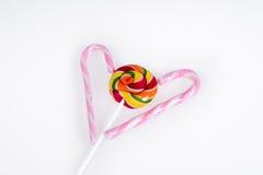 Bonbons - lucette colorée et rose avec le bâton blanc de rayures sur un fond blanc Photos libres de droits