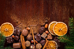 Bonbons à Noël : les chocolats, pralines, ont séché les anneaux, les épices et les écrous oranges Photos libres de droits