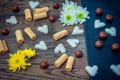Bonbons und Blumen auf dem Tisch Lizenzfreie Stockfotos