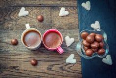 Bonbons und Schalen mit Kaffee auf dem Holztisch Lizenzfreies Stockbild