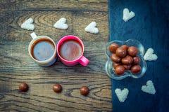 Bonbons und Schalen mit Kaffee auf dem Holztisch Lizenzfreies Stockfoto