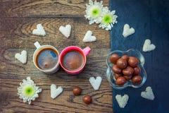 Bonbons und Schalen mit Kaffee auf dem Holztisch Stockbilder