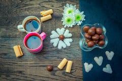 Bonbons und Schalen mit Kaffee auf dem Holztisch Lizenzfreie Stockbilder