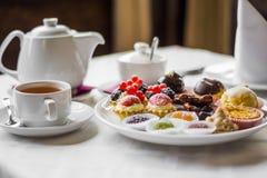 Bonbons und Tee durch ZVEREVA Stockfotos