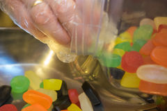 Bonbons von einem Glas heraus messen, das Plastikhandschuhe trägt Stockbild