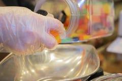 Bonbons von einem Glas heraus messen, das Plastikhandschuhe trägt Lizenzfreies Stockbild