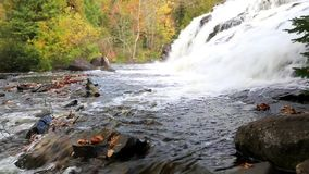 Bond Falls in autumn - Munising Michigan. Bond Waterfalls near Paulding in the Upper Peninsula of Michigan with a backdrop of autumn colors stock video footage