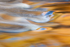 Bond Falls Rapids. Bond Falls cascade captured with motion blur and illuminated by reflected color from sunlit autumn maples and blue sky overhead, Michigan's Royalty Free Stock Photos