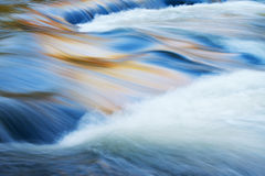 Bond Falls Rapids. Bond Falls cascade captured with motion blur and illuminated by reflected color from sunlit autumn maples and blue sky overhead, Michigan's Royalty Free Stock Images