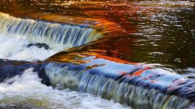 Bond Falls Reflecting Loop. Loop features brilliantly colorful fall foliage and a deep blue sky reflected on the water's surface at Bond Falls, a waterfall in stock footage